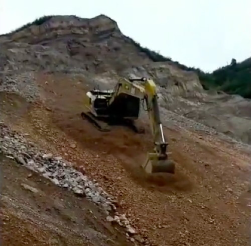 Excavator Glissades Down Mountain